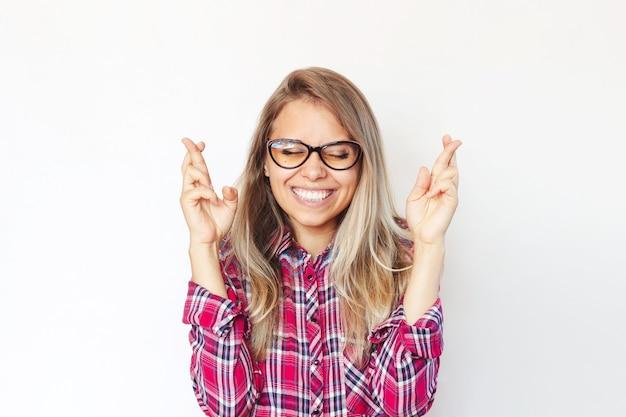 Una giovane donna bionda sorridente incrocia le dita per buona fortuna in attesa dei risultati della lotteria o degli esami