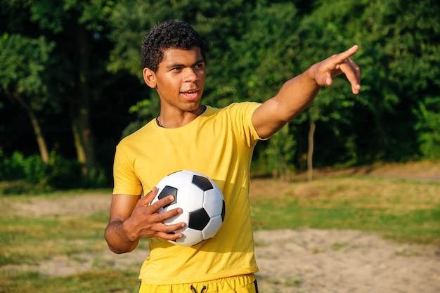 Il giovane brasiliano sorridente tiene una palla prima di giocare su una spiaggia sabbiosa erbosa