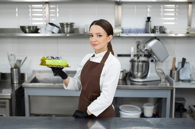 Il giovane chef bruna sorridente tiene una torta di mousse decorata con cioccolatini fatti a mano.