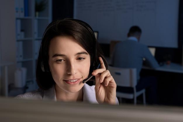 Giovane operatore bruna sorridente con auricolare guardando lo schermo del computer mentre consulta i clienti online in tarda serata