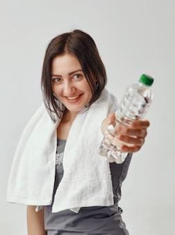 Giovane donna bruna sorridente in maglietta grigia che tiene l'asciugamano bianco intorno al collo e mostra una bottiglia d'acqua