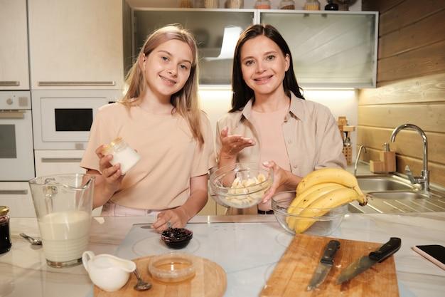 Giovane donna bruna sorridente e sua figlia adolescente che mostrano gli ingredienti del gelato fatto in casa mentre ti guardano