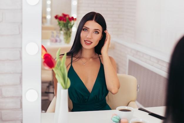 Giovane donna sorridente del brunette con la tazza di caffè che esamina lo specchio nel salone di parrucchiere