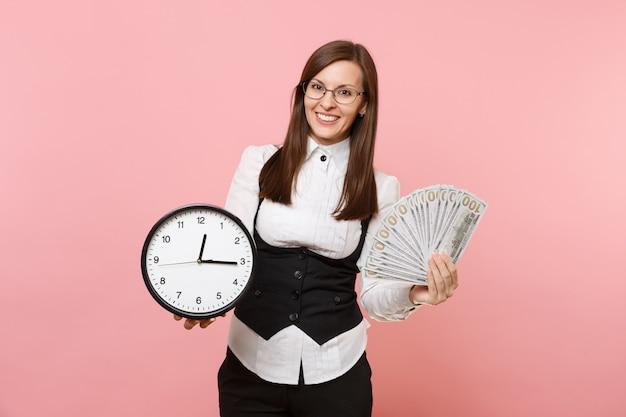 Giovane donna d'affari sorridente con gli occhiali che tengono un sacco di dollari, denaro contante e sveglia isolati su sfondo rosa. signora capo. ricchezza di carriera di successo. copia spazio per la pubblicità.