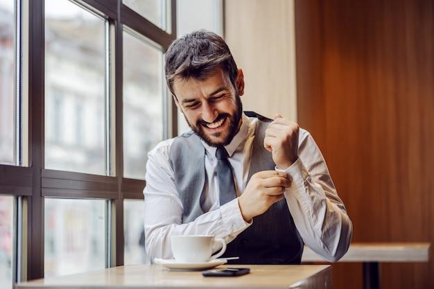 Giovane uomo d'affari sorridente che si siede nella caffetteria sulla pausa caffè e abbottona il gemello.