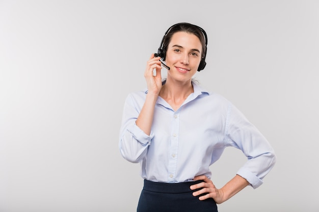Giovane imprenditrice sorridente in cuffia consulenza clienti mentre in piedi di fronte a voi in isolamento