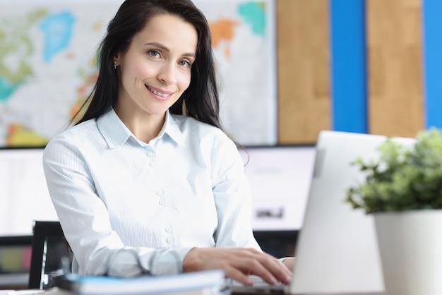 La giovane donna di affari sorridente si siede al computer portatile in ufficio