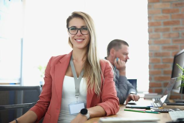La giovane donna d'affari sorridente si siede al tavolo di lavoro sullo sfondo dell'ufficio commerciale