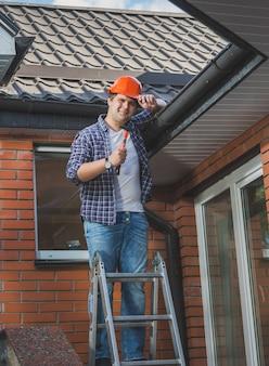 Giovane carpentiere sorridente che posa con il martello sulla scaletta sotto il tetto the