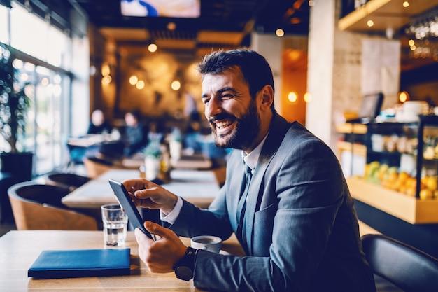 Giovane imprenditore di successo caucasico barbuto sorridente seduto nella caffetteria e utilizzando tablet per leggere importanti messaggi di posta elettronica.