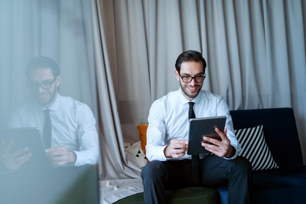 Giovane imprenditore caucasico sorridente in abbigliamento formale utilizzando tablet per lavoro e seduto sul divano in ufficio.