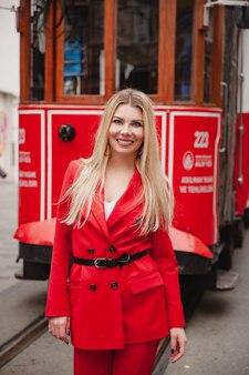 Giovane donna turistica caucasica sorridente che rimane davanti al tram rosso sulla via istiklal a istanbul