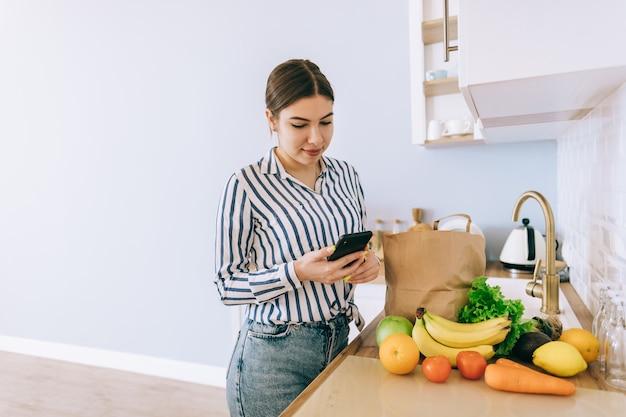 La giovane donna caucasica sorridente utilizza lo smartphone nella cucina moderna, borsa con verdura fresca sul tavolo. acquisto online di cibo e generi alimentari.