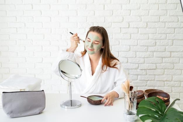 Giovane donna caucasica sorridente che indossa accappatoi applicando maschera di argilla guardando allo specchio