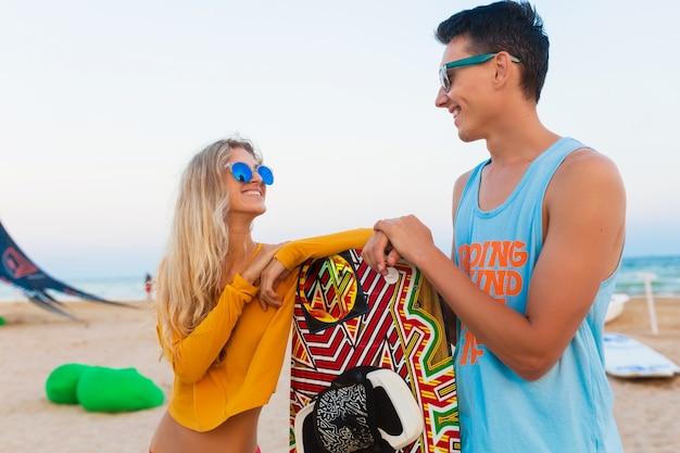 Giovane coppia sorridente che si diverte sulla spiaggia con la tavola da kitesurf durante le vacanze estive