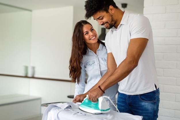 Giovane coppia sorridente a casa che fa le faccende domestiche e stira