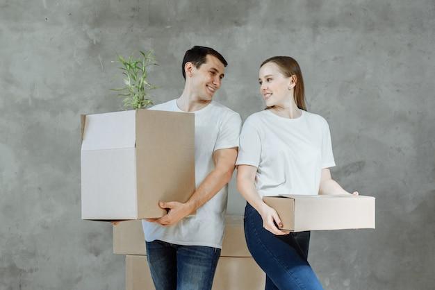Giovane coppia sorridente uomo e donna in mano con scatole per trasferirsi in un nuovo appartamento.