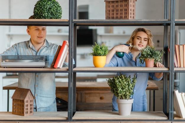Giovani coppie sorridenti allo scaffale con piante domestiche