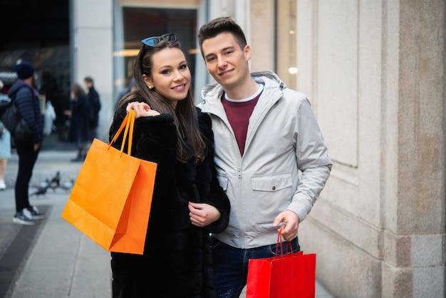 Giovane coppia sorridente che fa shopping in una strada urbana