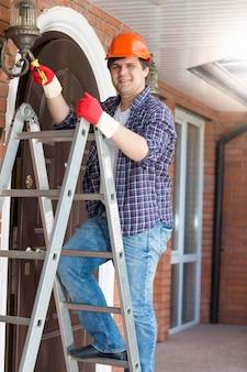 Giovane elettricista sorridente in piedi su una scala a pioli e che ripara una lampada da esterno