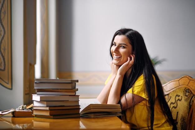 Giovani libri di lettura sorridenti ed entusiasti della studentessa alla vecchia biblioteca