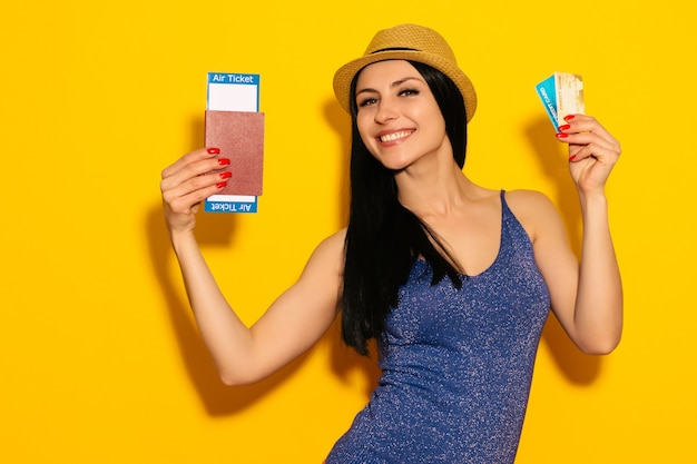 Giovane studentessa eccitata sorridente in possesso di passaporto biglietto d'imbarco e carta di credito