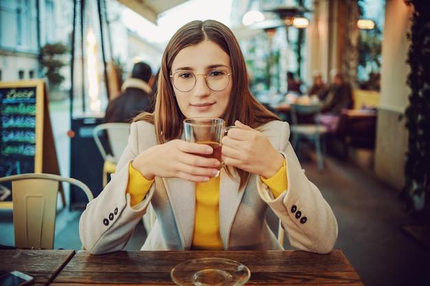Giovane bruna alla moda sorridente che si siede sulla terrazza di un bar, che tiene tazza di tè e che guarda l'obbiettivo.