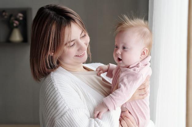 Giovane donna sorridente che guarda un bambino adorabile sulle sue braccia
