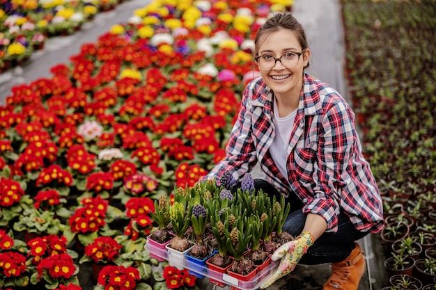Giovane operaio femminile sorridente del giardino della scuola materna che si accovaccia e che tiene cassa con i fiori. tutt'intorno a lei ci sono tutti i tipi di fiori colorati.