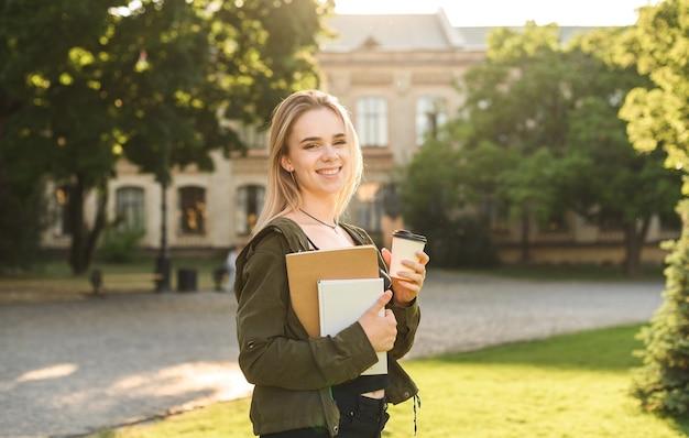La giovane studentessa sorridente che tiene porta via il caffè nel parco vicino all'università