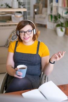 Giovane femmina sorridente con una tazza di tè che si siede sulla sedia a rotelle davanti allo schermo del computer e comunica con l'insegnante in linea alla lezione