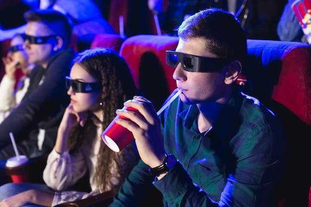 Giovani amici sorridenti in vetri 3d che mangiano popcorn e che guardano film in cinema