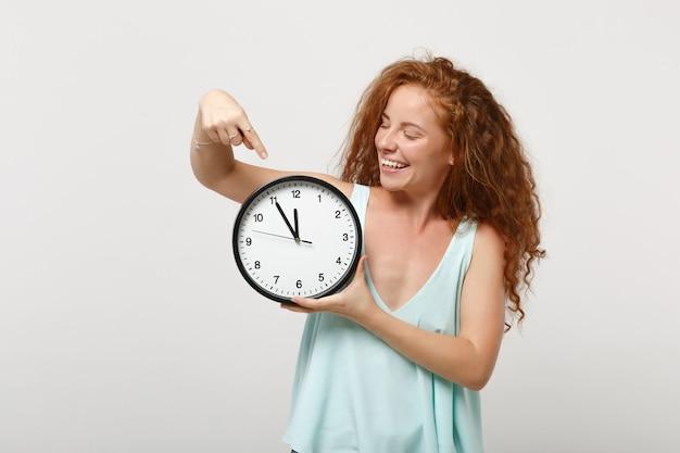 Giovane ragazza sorridente divertente della donna della testarossa in vestiti leggeri casuali che posano isolato sul fondo bianco della parete, ritratto dello studio. concetto di stile di vita della gente. mock up copia spazio. dito indice puntato sull'orologio.