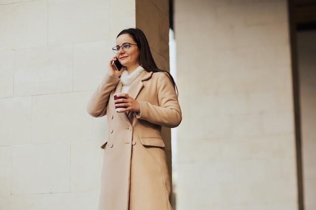 Giovane ragazza sorridente in cappotto beige e occhiali da vista parlando sullo smartphone e bevendo caffè in città vicino all'edificio.