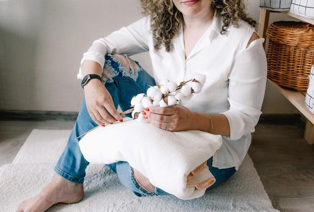 Una giovane ragazza sorridente in abiti primaverili alla moda alla moda è seduta sul pavimento con un rametto di cotone in fiore tra le mani.