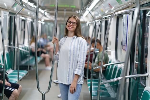 Giovane ragazza sorridente all'interno dell'auto della metropolitana tenere sul corrimano studentessa allegra che viaggia in metropolitana
