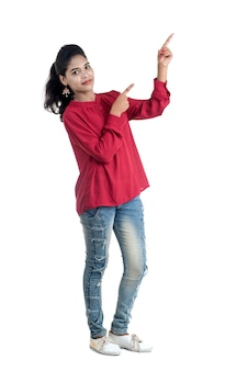 Giovane ragazza sorridente che punta le dita per copiare lo spazio su uno sfondo bianco