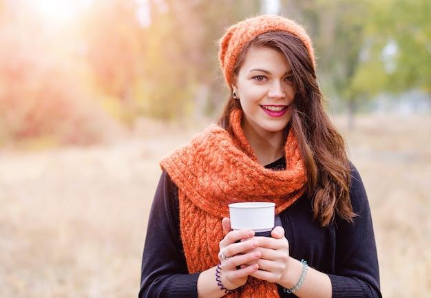 Giovane ragazza sorridente in una sciarpa e un cappello con una tazza di caffè (tè) nelle mani dell'autunno all'aperto. i raggi del sole illuminano il modello da dietro.