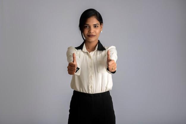 Giovane ragazza sorridente che mostra segno giusto o pollice in alto su uno sfondo grigio