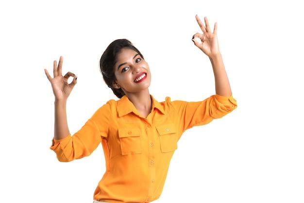 Giovane ragazza sorridente che mostra segno giusto o pollice in alto su uno sfondo bianco