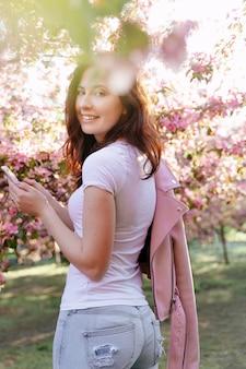 Una giovane ragazza sorridente sta con un telefono in mano in un giardino fiorito di mele e ciliegi