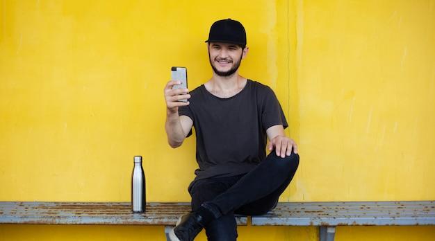 Il giovane ragazzo sorridente è seduto dietro il giallo e sta prendendo selfie con lo smartphone vicino alla sua bottiglia termica per l'acqua.