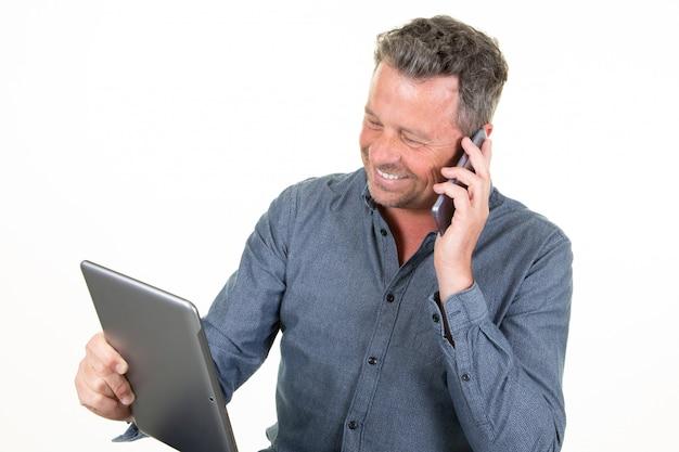 Uomo caucasico felice sorridente dei giovani che utilizza compressa e che chiama nel telefono cellulare isolato sul fondo bianco dello studio