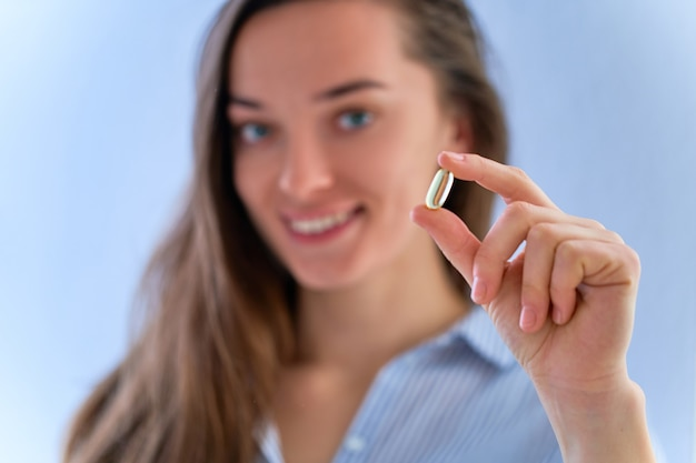 Giovane donna felice sorridente che prende integratore alimentare vitamina omega 3 per la salute. softgel di olio di pesce, vitamina d e vitamina c per sostenere l'immunità e la prevenzione delle malattie