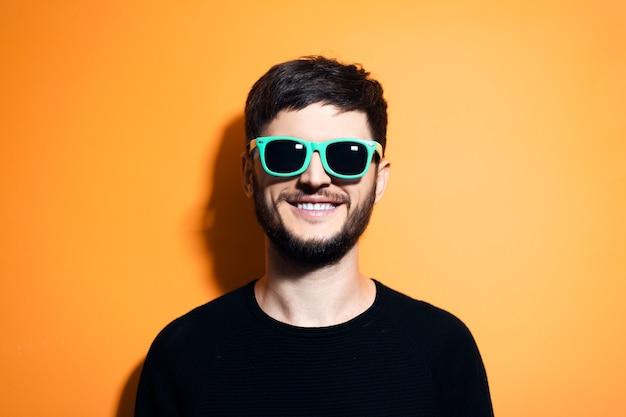 Giovane hipster sorridente con occhiali da sole aqua menthe sulla parete arancione.