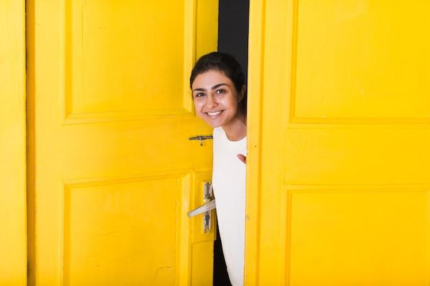 Giovane donna indiana sorridente che sbircia attraverso la porta aperta gialla
