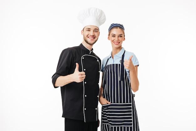 Il giovane cuoco unico sorridente in uniforme nera e cappello bianco e donna graziosa cucina felicemente in grembiule e cappuccio a strisce