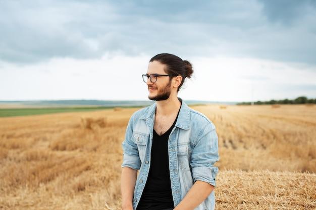 Giovane uomo sorridente in giacca di jeans in piedi nel campo di fattoria vicino a mucchi di fieno.