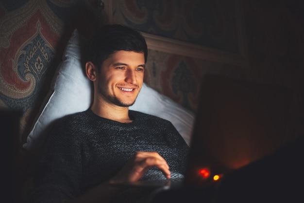 Giovane uomo sorridente sdraiato sul letto con il portatile in camera oscura a casa.
