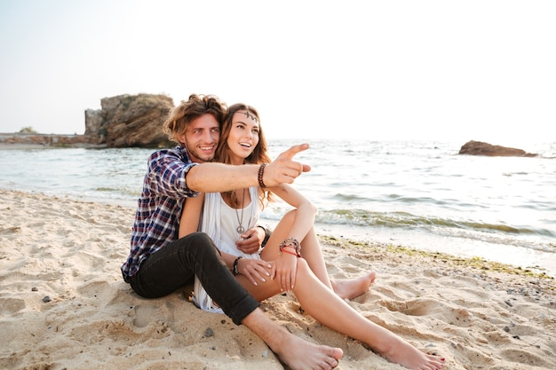 Giovane uomo sorridente che punta il dito contro qualcosa mentre è seduto in spiaggia con la sua ragazza